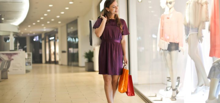 A young blonde woman wearing a purple red dress and carrying shopping bags looks at a shop display